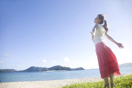 青空の下で両手を広げ太陽の光を浴びる女性